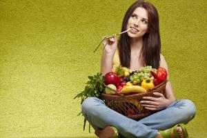 Девушка сидит с корзиной фруктов и овощей